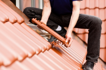 home repair: Roofing - construction worker standing on a roof covering it with tiles