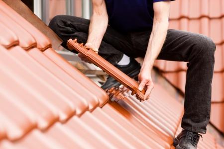 Toitures - travailleur de la construction debout sur un toit couvrant avec tuiles