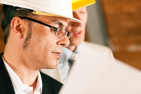 Architect and construction engineer or surveyor discussion plans and blueprints. Both are wearing hardhats and are standing on the construction site of a home indoors Stock Photo - 10260979