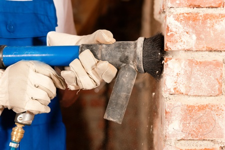 removing: Construction worker removing the plaster from a brick wall in the course of a renovation or restoration of a building