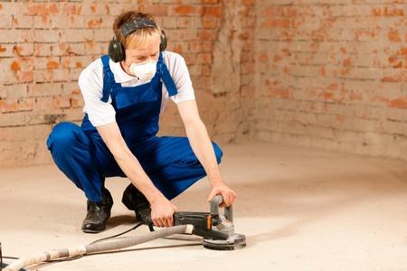 meuleuse: Travailleur de la construction travaillant moudre le sol en ciment