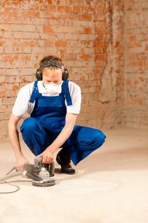 cowering: Construction worker working grinding the cement floor   Stock Photo