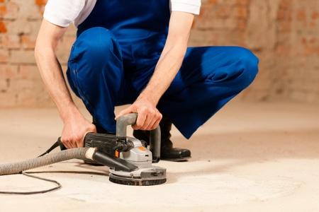 grind: Trabajador de la construcci�n trabajan pulido el piso de cemento Foto de archivo