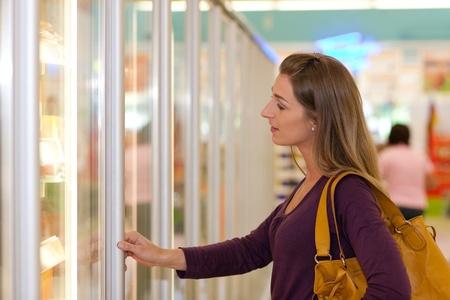 comida congelada: Mujer en un pie de supermercado delante del congelador buscando su alimento favorito de congelados