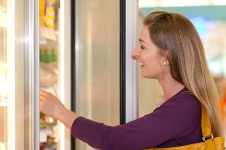 Woman in a supermarket standing in front of the freezer looking for her favorite frozen food Stock Photo - 10261006