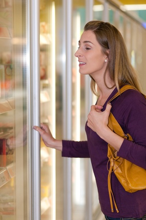 Woman in a supermarket standing in front of the freezer looking for her favorite frozen food Stock Photo - 10261028