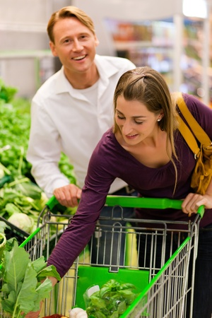 Man and woman in a supermarket at the vegetable shelf shopping for groceries, she is putting some stuff into the shopping cart  Stock Photo - 10261022