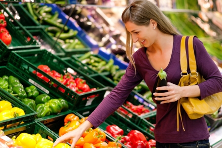 vegetables supermarket: woman in a supermarket at the vegetable shelf shopping for groceries, she is choosing  Stock Photo