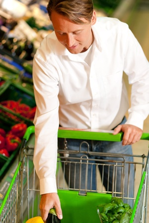 Man in a supermarket at the vegetable shelf shopping for groceries, he is putting some stuff into the shopping cart Stock Photo - 10261003