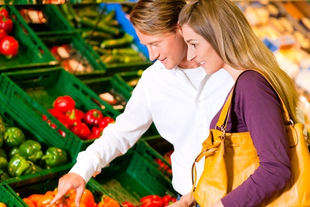 Couple in a supermarket at the vegetable shelf shopping for groceries, they are checking out the groceries Stock Photo - 10261024