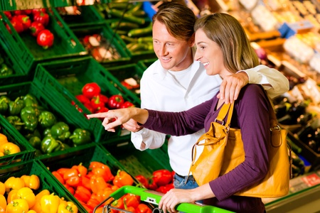 Couple in a supermarket at the vegetable shelf shopping for groceries, they are checking out the groceries Stock Photo - 10261026