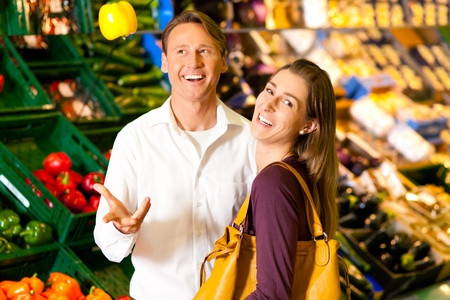 Couple in a supermarket at the vegetable shelf shopping for groceries, they are checking out the groceries photo