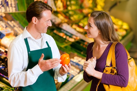 woman in a supermarket at the vegetable shelf shopping for groceries, a shop assistant is helping her  photo