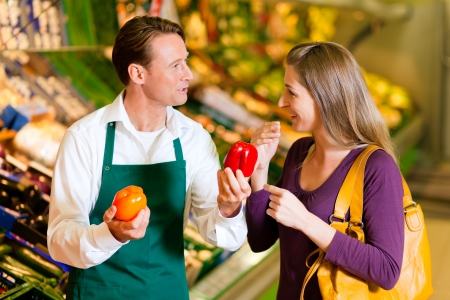 selling service: woman in a supermarket at the vegetable shelf shopping for groceries, a shop assistant is helping her
