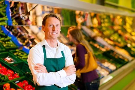 estanterias: Asistente de tienda en un supermercado en la plataforma de vegetal; en el fondo una mujer elegir verduras