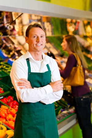 Shop assistant in a supermarket at the vegetable shelf; in the background a woman choosing vegetables Stock Photo - 10260898