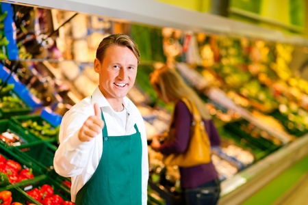 selling service: Shop assistant in a supermarket at the vegetable shelf; in the background a woman choosing vegetables Stock Photo