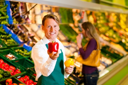 Shop assistant in a supermarket at the vegetable shelf; in the background a woman choosing vegetables Stock Photo - 10260992