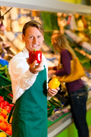 Shop assistant in a supermarket at the vegetable shelf; in the background a woman choosing vegetables Stock Photo - 10260912