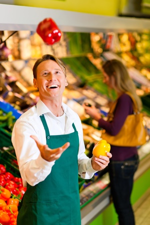 selling service smile: Shop assistant in a supermarket at the vegetable shelf; he is tossing a bell pepper Stock Photo