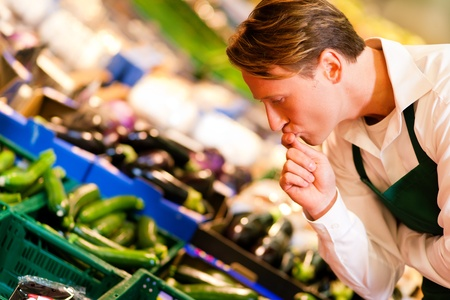 food inspection: Shop assistant in a supermarket at the vegetable shelf inspecting the stuff for sale Stock Photo