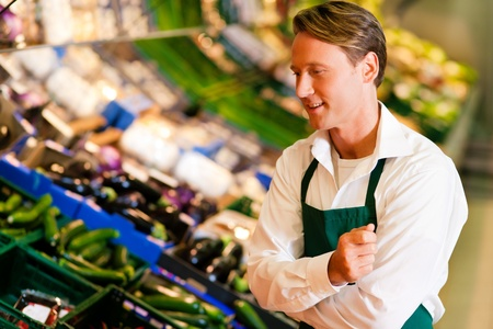 Shop assistant in a supermarket at the vegetable shelf inspecting the stuff for sale Stock Photo - 10260960