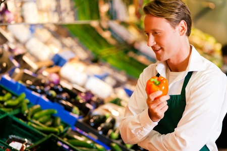 store clerk: Shop assistant in a supermarket at the vegetable shelf inspecting the stuff for sale Stock Photo
