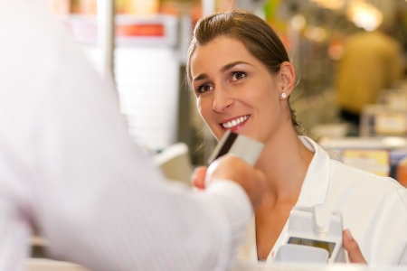 Male customer in supermarket handing his credit card to cashier at the checkout desk in order to pay Stock Photo - 10260889