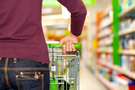 supermarket shelves: Woman in a supermarket running trough the aisle with a shopping cart  Stock Photo
