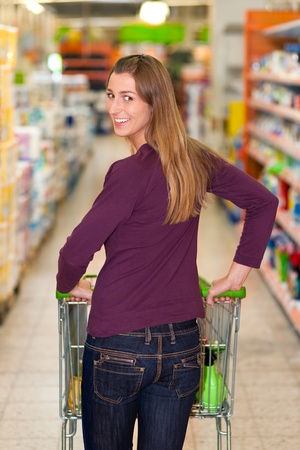 Woman in a supermarket running trough the aisle with a shopping cart Stock Photo - 10260952