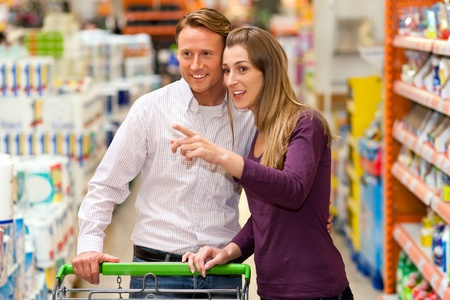 Couple in a supermarket shopping equipped with a shopping cart buying groceries and other stuff, they are looking for what they need  photo