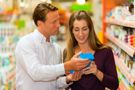 description: Couple in a supermarket shopping groceries and other stuff, they are looking for what they need  Stock Photo