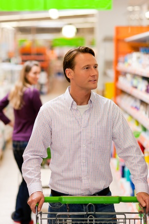 Woman in the supermarket looking after a guy she just met shopping there, she is ready to flirt a bit   photo