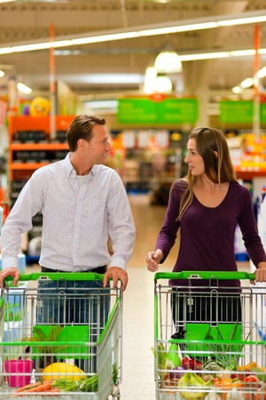 Couple in a supermarket shopping equipped with shopping carts buying groceries; they almost finished   photo