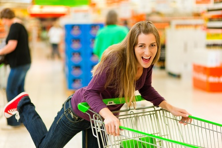 Woman in a supermarket running trough the aisle with a shopping cart and having fun photo