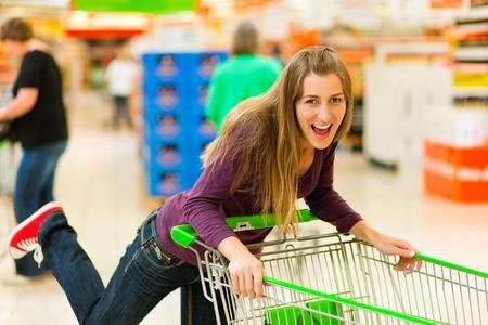 Mujer en un supermercado ejecutando a través del pasillo con un carrito de compras y divertirse