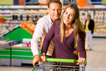Couple in a supermarket shopping equipped with a shopping cart buying groceries and other stuff, they are both having fun with the store and each other  Stock Photo - 10261029