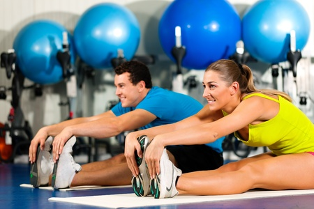 warming: couple in colorful cloths in a gym doing aerobics or warming up with gymnastics and stretching exercises