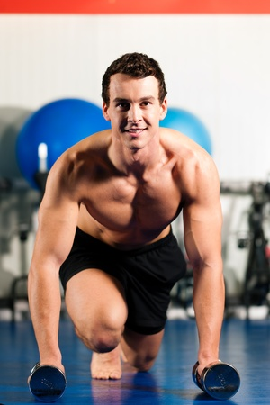 Very strong and muscular man exercising by starting pushups in a gym Stock Photo - 10269890