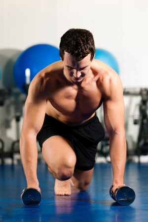 Very strong and muscular man exercising by starting pushups in a gym   photo