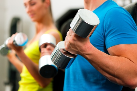 man lifting weights: couple in the gym, rivaling each other, exercising with dumbbells