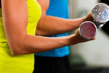 levantando pesas: Pareja en el gimnasio, rivalizando entre sí, en el ejercicio con pesas