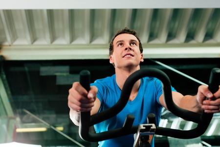 kardio: Man forog az edzőteremben, gyakorlása lába kardió képzés kerékpár Stock fotó
