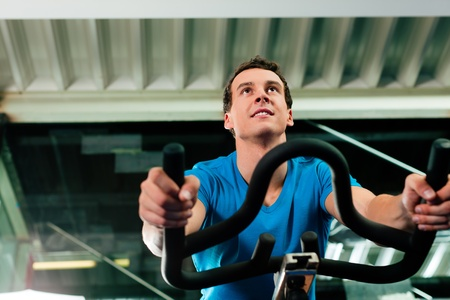 Man spinning in the gym, exercising his legs doing cardio training on bicycle photo