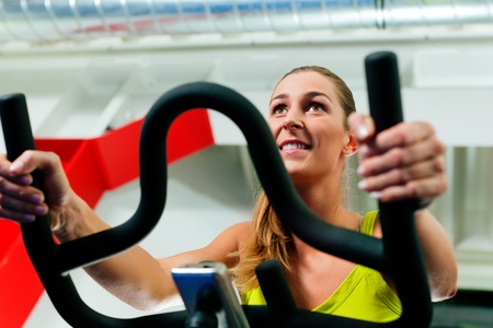cardio fitness: Woman spinning in the gym, exercising their legs doing cardio training on bicycle