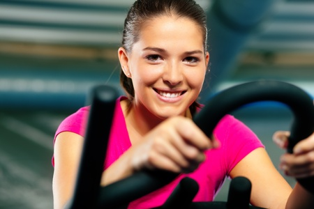 Woman spinning in the gym, exercising their legs doing cardio training on bicycle photo