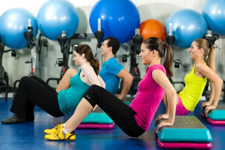 aerobic instructor: Fitness People in gym on step board; strengthening the abdominal muscles   Stock Photo