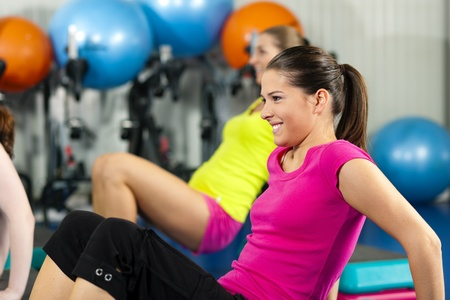 fitness instructor: Fitness People in gym on step board; strengthening the abdominal muscles   Stock Photo