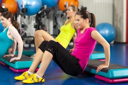 gimnasia aerobica: Gente de fitness en el gimnasio de la Junta de paso; fortalecimiento de los m�sculos abdominales   Foto de archivo
