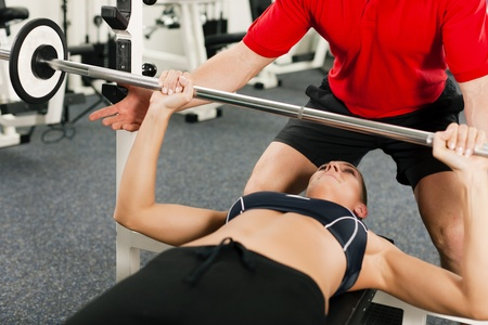 personal training: Woman in gym with personal fitness trainer exercising power gymnastics with a barbell